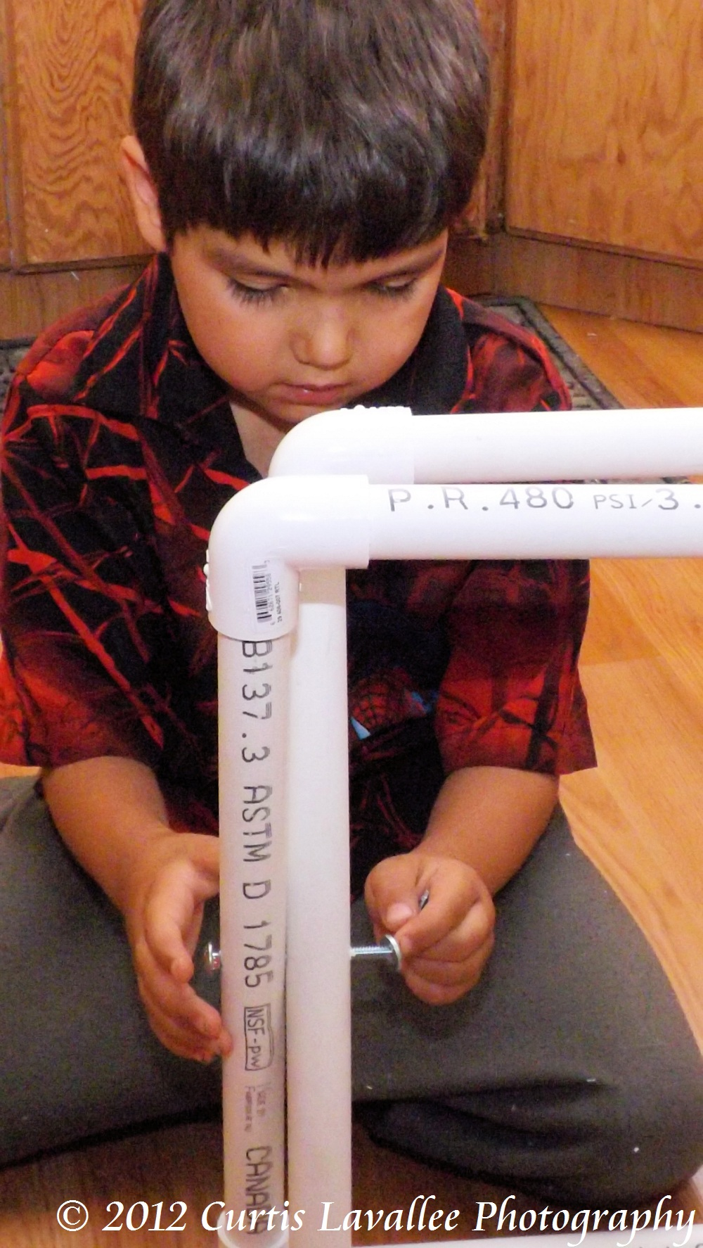 boy putting a bolt through pvc pipe