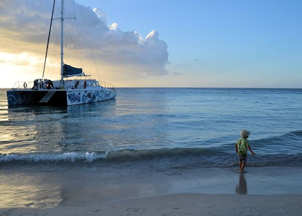 boy and catamaran ocean jamaica