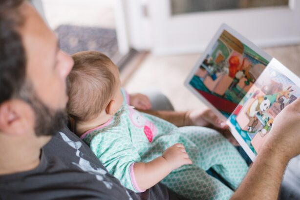 man and baby reading